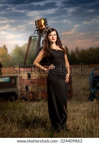 Beautiful young woman posing at early morning at hot air balloon gondola - stock photo