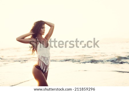 beautiful young woman posing at sandy beach at sunset  - stock photo