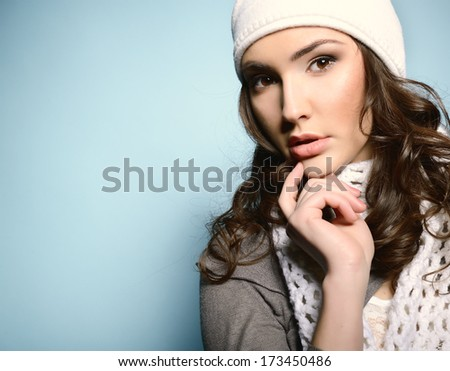 Beautiful young woman posing at studio in white nat and scarf - stock photo