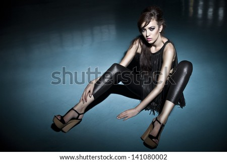 Beautiful young woman posing fashion in airport shed standing down in black dress