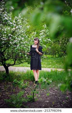 Beautiful young woman posing in a flowering spring park.