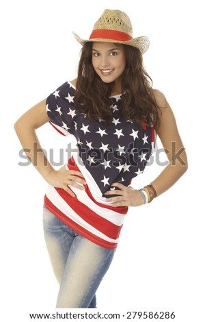 Beautiful young woman posing in American flag t-shirt and straw hat, hand on hip, smiling happy. - stock photo