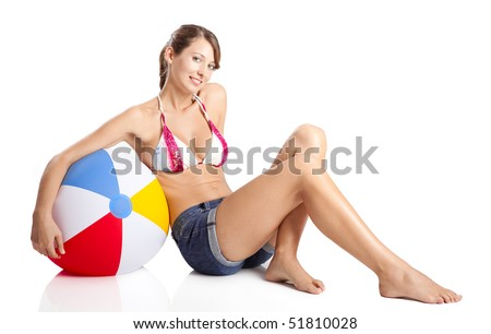 Beautiful young woman posing in bikini with a beach ball - stock photo