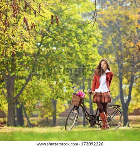 Beautiful young woman posing in park with her bicycle, shot with tilt and shift lens - stock photo