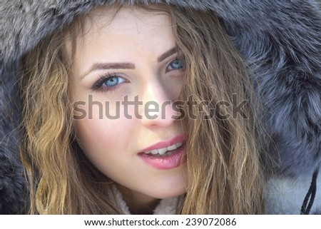 Beautiful young woman posing in the snow