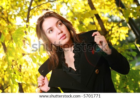 Beautiful young woman posing in yellow autumn forest. - stock photo