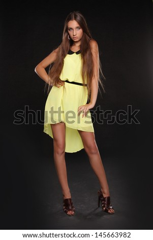 Beautiful young woman posing in yellow dress isolated on black background - stock photo