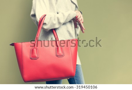 Beautiful young woman posing, jeans, red big handbag and sweater next to the wall