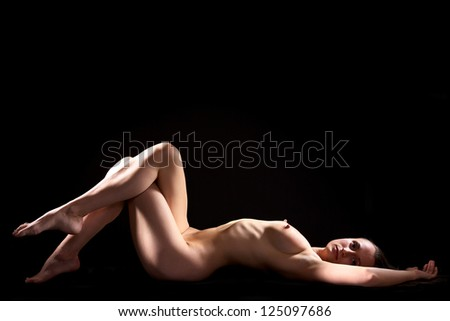 Beautiful young woman  posing nude on black - stock photo