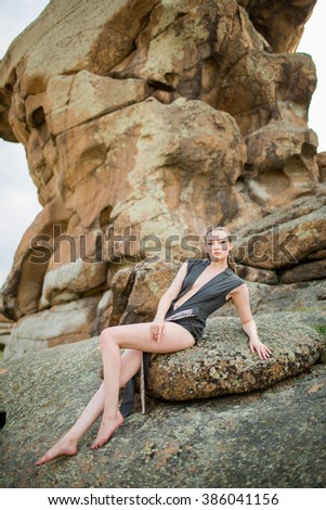 Beautiful young woman posing over picturesque landscape. - stock photo