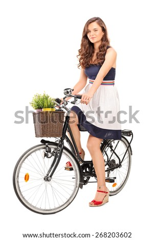 Beautiful young woman posing seated on a black bicycle with a basket in the front, carrying two flowerpots isolated on white background - stock photo