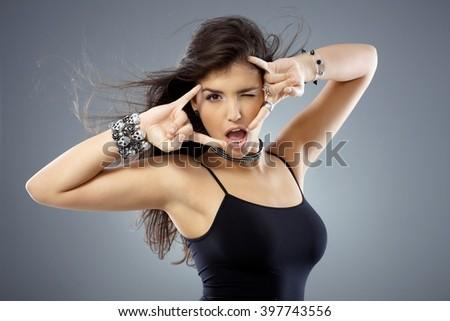 Beautiful young woman posing showing rock on hand gesture with both hands and winking. - stock photo