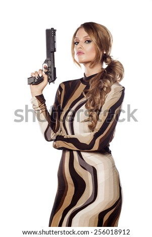 Beautiful young woman posing with a gun - stock photo