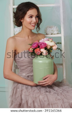 Beautiful young woman posing with flowers on the white background. Very gentle look of the model. Beautiful makeup. Elegant and sensual model.