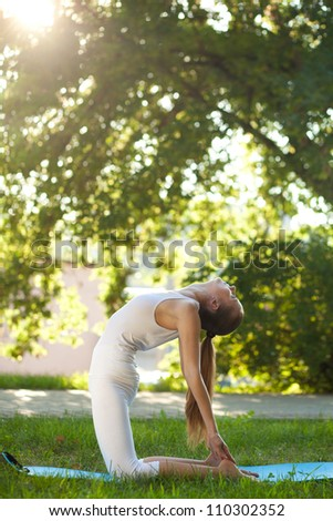 Beautiful young woman practices yoga in nature; standing on her knees, arching back and keeping her feet hands