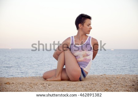 Beautiful young woman practicing yoga on mat outdoors on sand