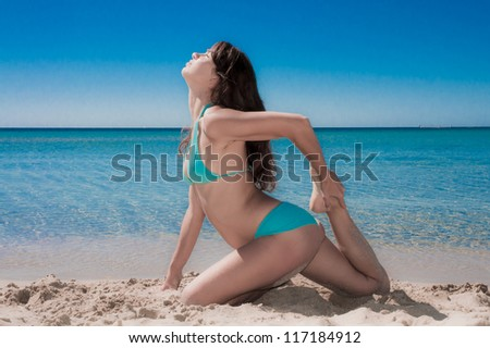 Beautiful young woman practicing yoga on sea beach