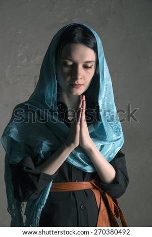 Beautiful young woman praying - stock photo
