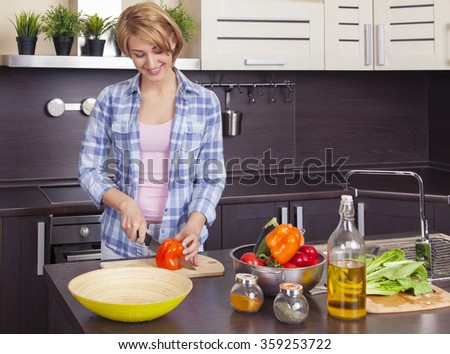 beautiful young woman preparing a salad in the kitchen. Horizontal image. Overall plan. - stock photo