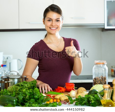 Beautiful young woman preparing vegetarian meal and smiling at home