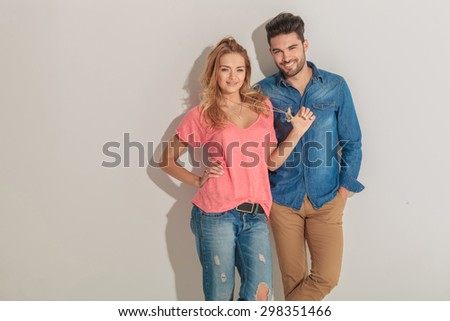Beautiful young woman pulling her necklace while her lover is holding his hands in pockets. - stock photo