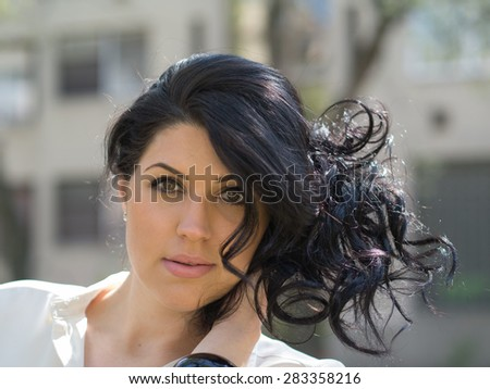 beautiful young woman ran a hand through her black hair