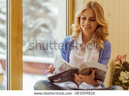 Beautiful young woman reading a magazine and smiling while sitting on the window sill - stock photo