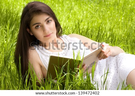 Beautiful young woman reading book in spring garden