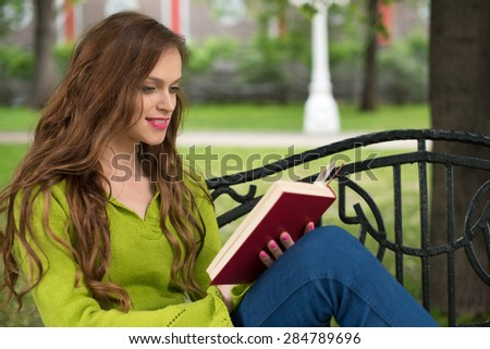 beautiful young Woman Reading book in the Park - stock photo
