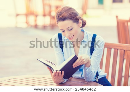Beautiful young woman reading book outdoors. Positive face expression  - stock photo