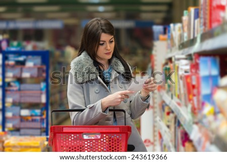 Beautiful Young Woman Reading Her Shopping List In Produce Department Of A Grocery Store - Supermarket - Shallow Deep Of Field - stock photo