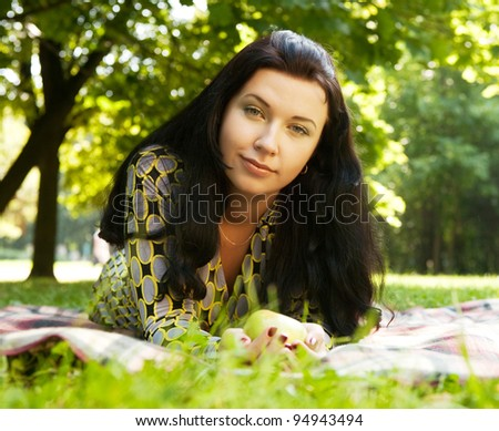Beautiful young woman reading outdoor, lying on a blanket