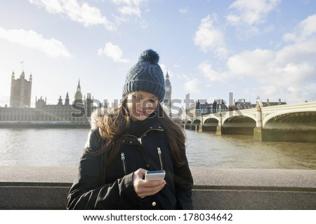 Beautiful young woman reading text message through smart phone by river Thames; London; UK - stock photo