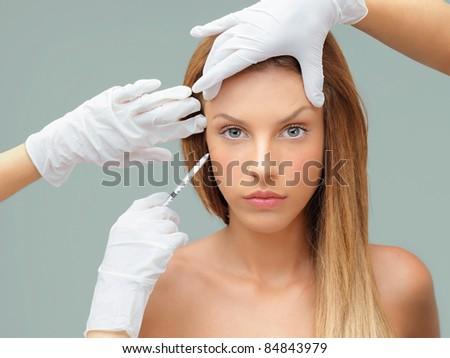 beautiful young woman receiving an injection eye area - stock photo