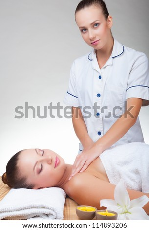 Beautiful young woman receiving massage of body in spa salon - stock photo