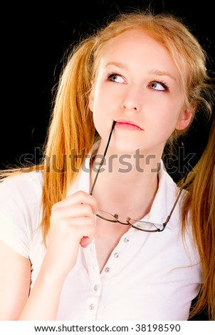 Beautiful young woman reflects on meaning of life, is isolated on black background.