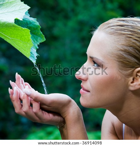 Beautiful young woman refreshing herself with clear water from a leaf in the nature. Symbol of purity, body care and nature harmony