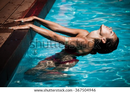 beautiful young woman relax and enjoy in pool, hot summer day, natural light, side view - stock photo