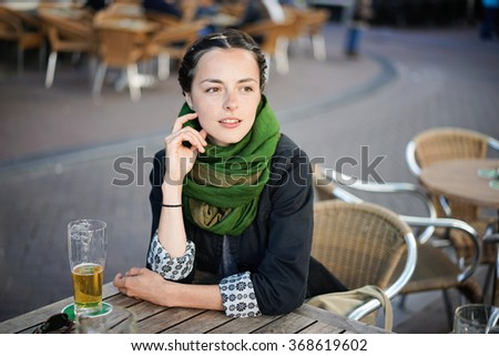 Beautiful young woman relaxes at a beer on a terrace in downtown