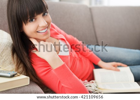 Beautiful young woman relaxing at home on the sofa and reading a book, she is smiling at camera
