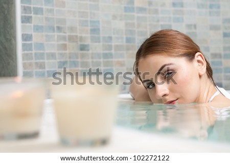 Beautiful young woman relaxing in a jacuzzi at thermal spa club - stock photo