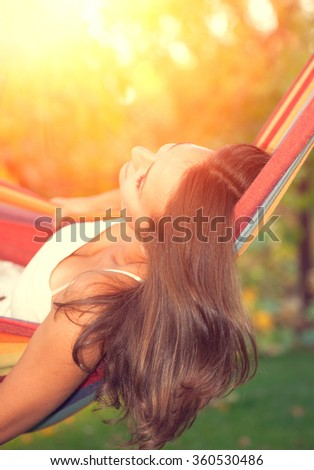 Beautiful Young Woman relaxing in hammock - stock photo