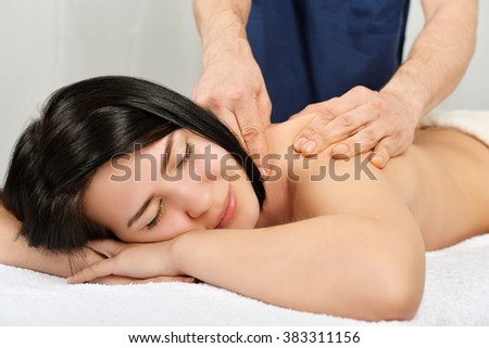 Beautiful young woman relaxing in spa with back massage - stock photo