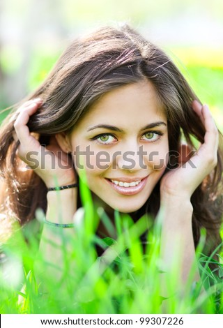 beautiful young woman relaxing in summer park - stock photo