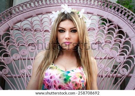 Beautiful Young Woman Relaxing In The Garden With Pink Chair - stock photo