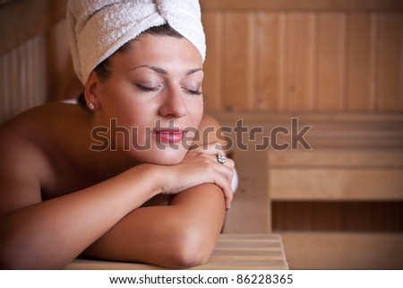Beautiful young woman relaxing in the sauna - stock photo
