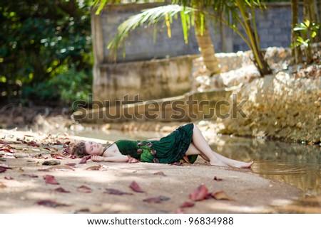 Beautiful young woman relaxing near lake - stock photo