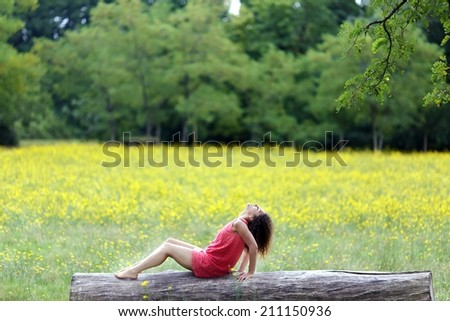 Beautiful young woman relaxing on a log or tree trunk in a rural field of dandelions.