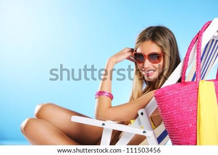 Beautiful young woman relaxing on beach chair - stock photo
