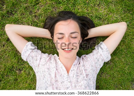 beautiful young woman relaxing on green grass with hands under head and eyes closed - stock photo